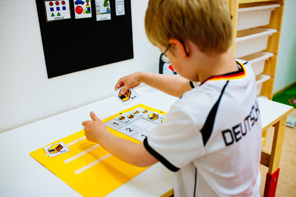 Bild wo ein Junge eine Therapiestunde hat und Bilder ordnet