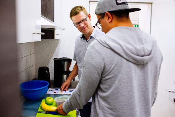 Hier sehen Sie zwei Personen die in der Küche was zubereiten.
