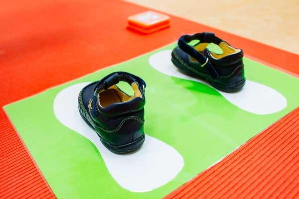 Hier sehen Sie ein Bild von Kinderschuhen der auf einen Abdruck von erwachsenen Schuhen steht.